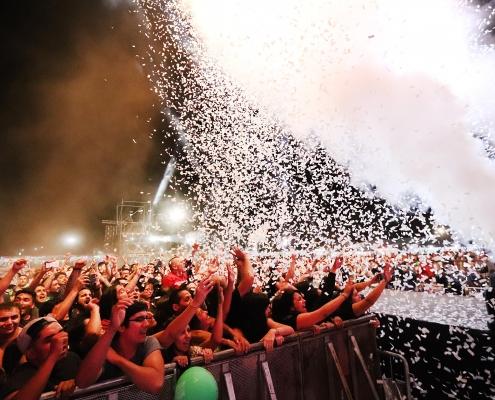 En esta imagen se muestra el público de la Semana Peñaflorina asitiendo a uno de los espectáculos. Se ve un grupo de gente, mientras tiran espuma desde el escenario